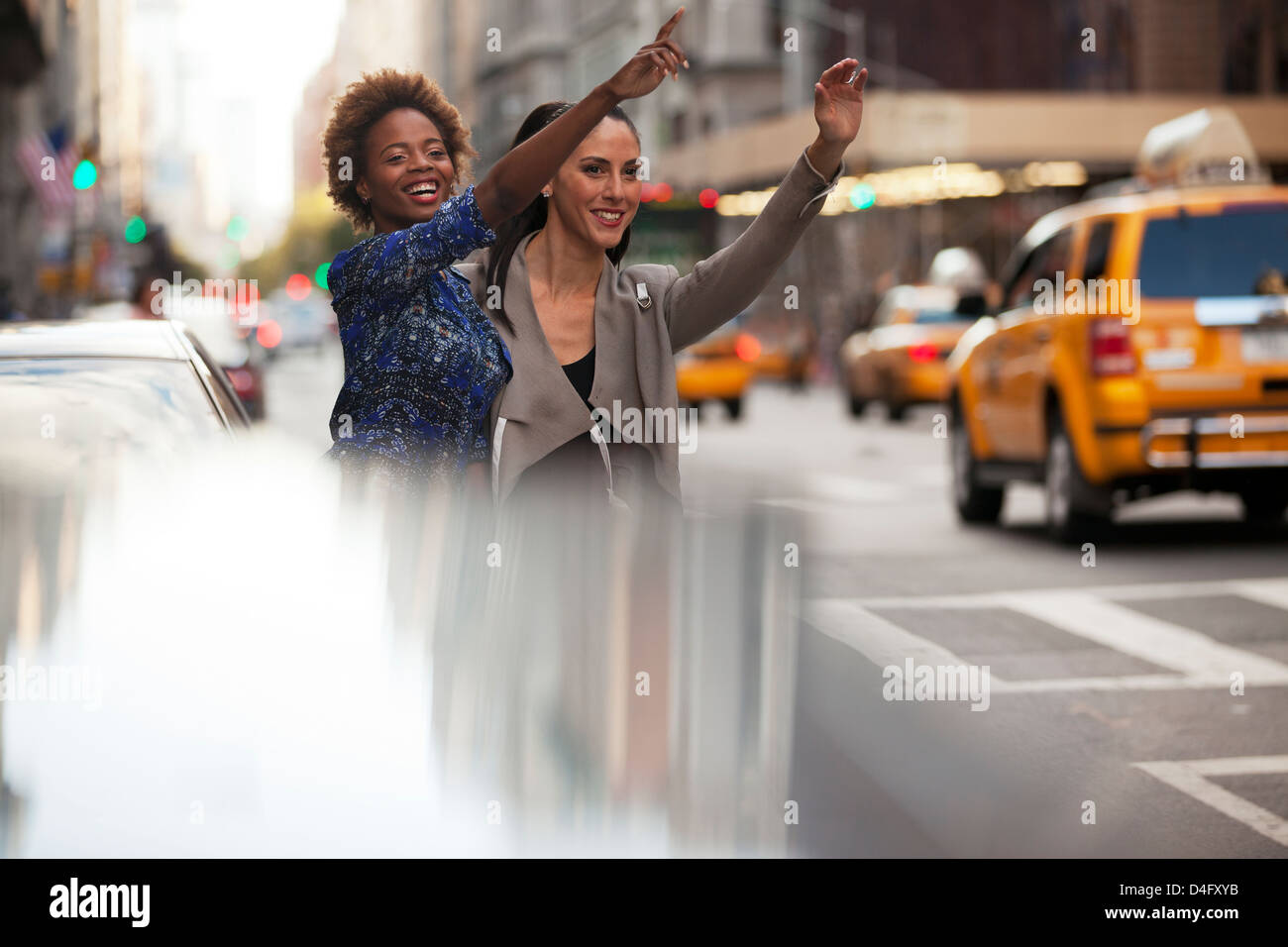 Women hailing taxi on city street - Stock Image
