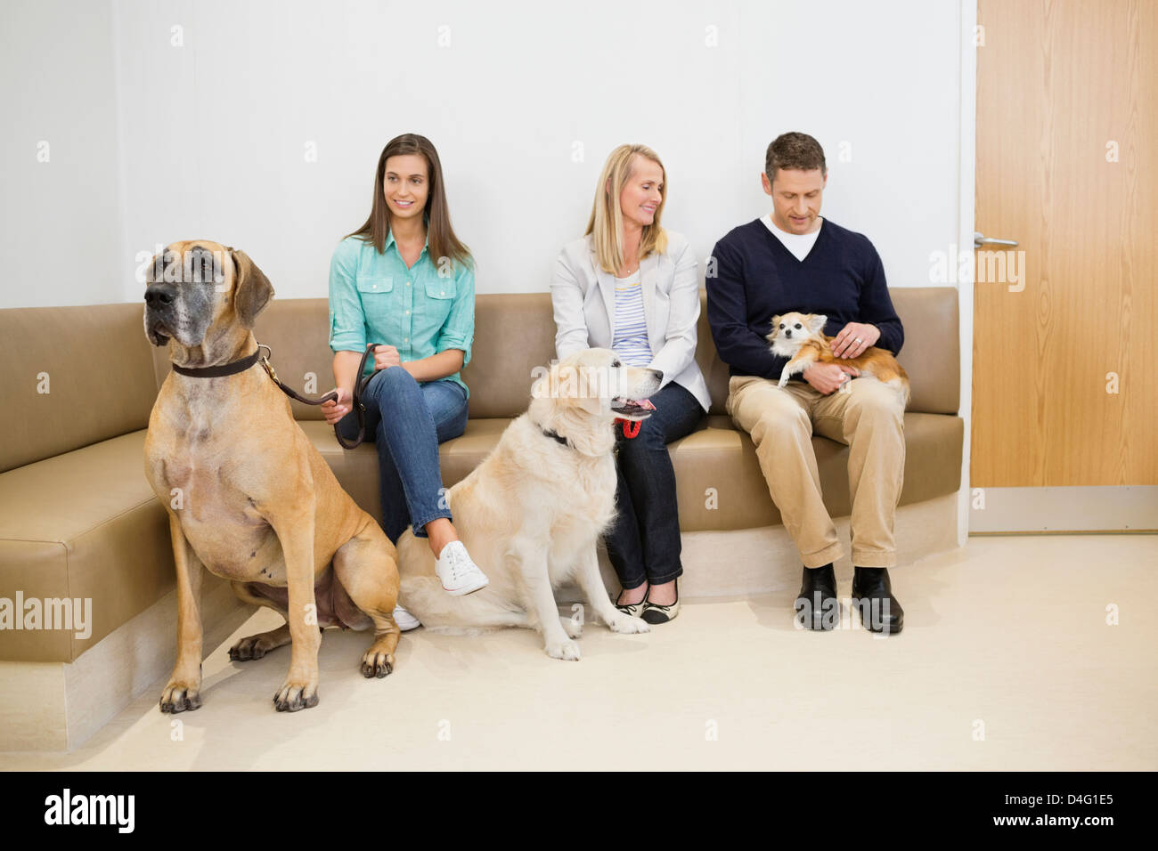 Owners with pet in waiting area†of vet's - Stock Image