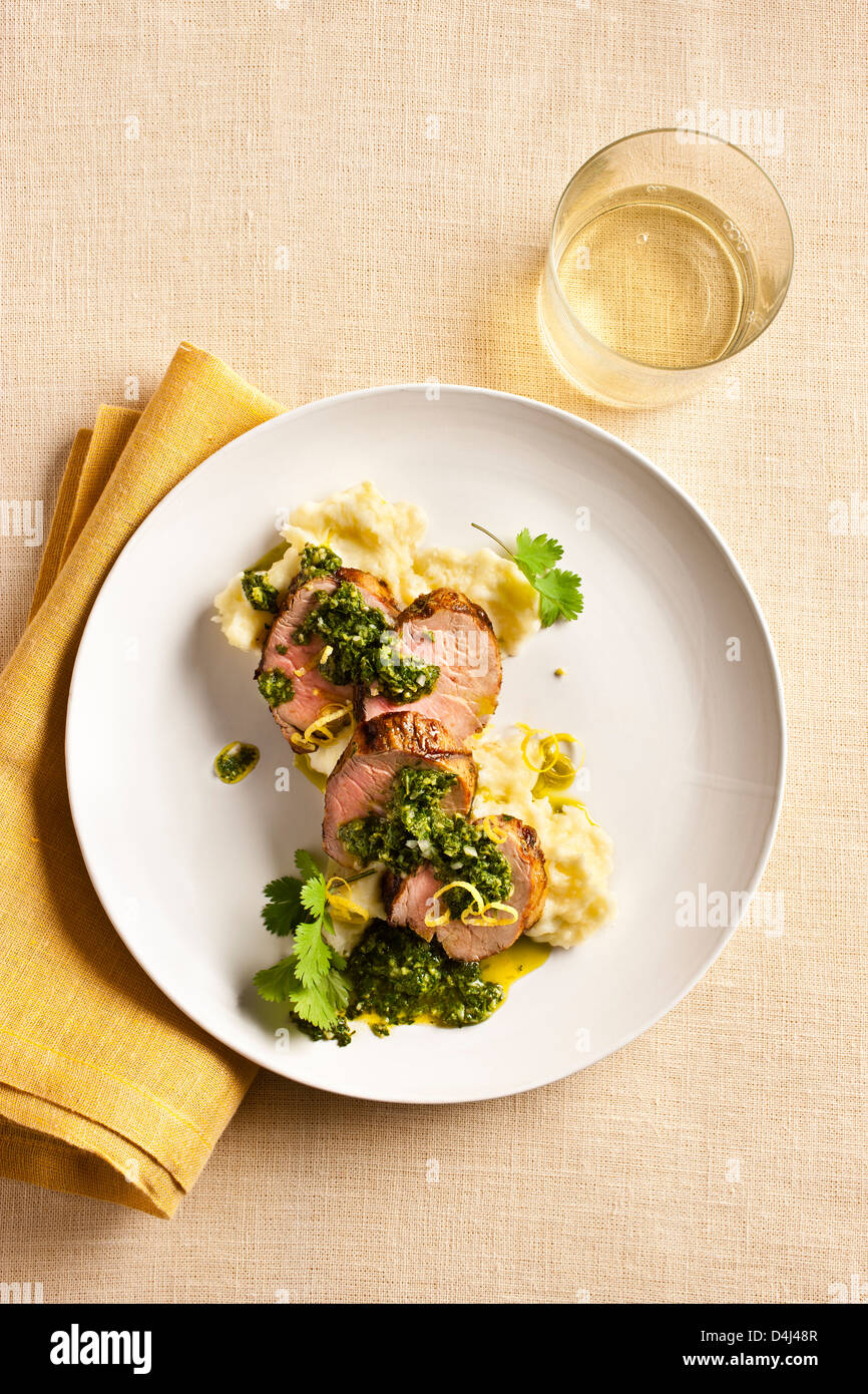 Grilled Pork Tenderloin sliced and served on Potato Puree with Chimichurri sauce. - Stock Image