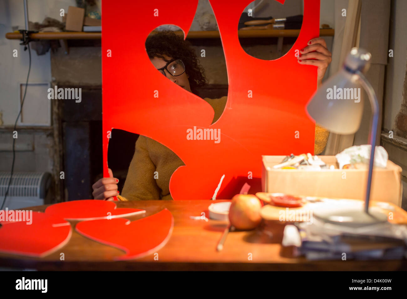 Artist cutting out red cardboard - Stock Image