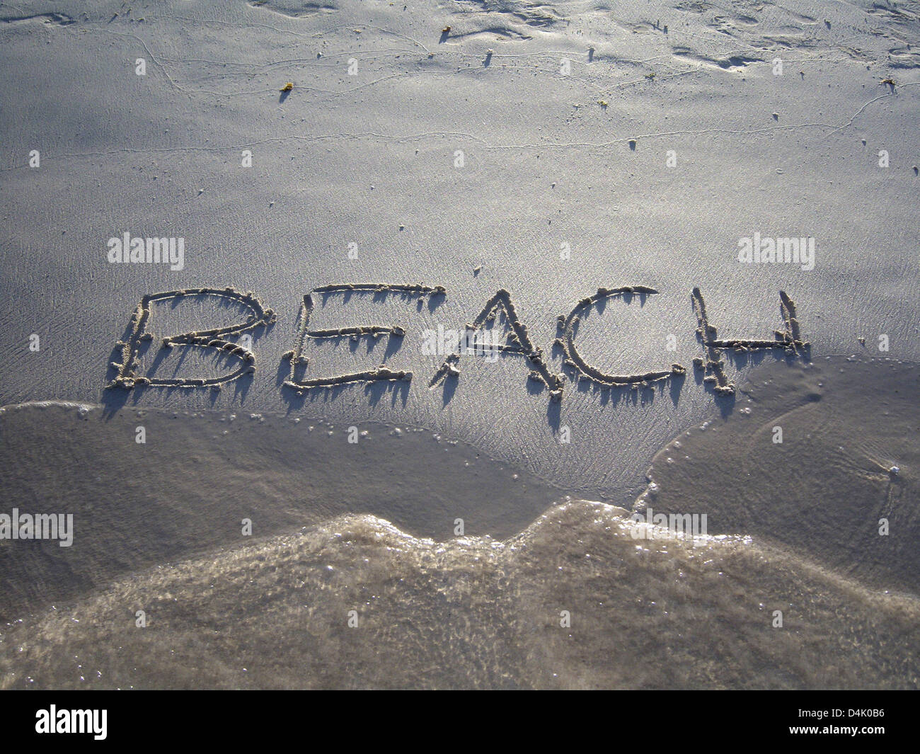 This picture of 2008 shows the lettering ?Beach? that is written into the sand but will be washed away by a wave Stock Photo