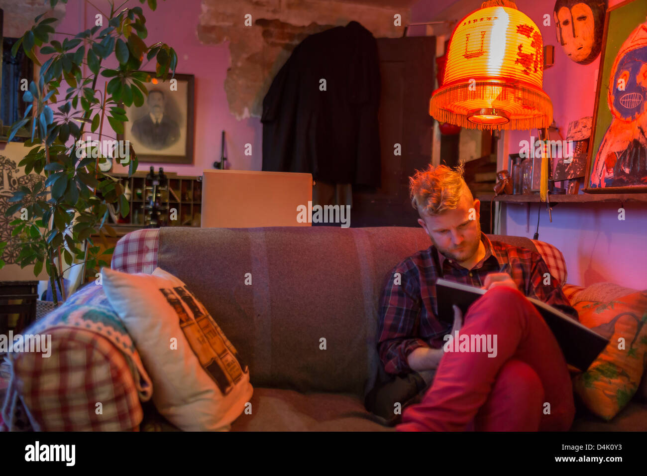 Man sketching under orange lamp - Stock Image
