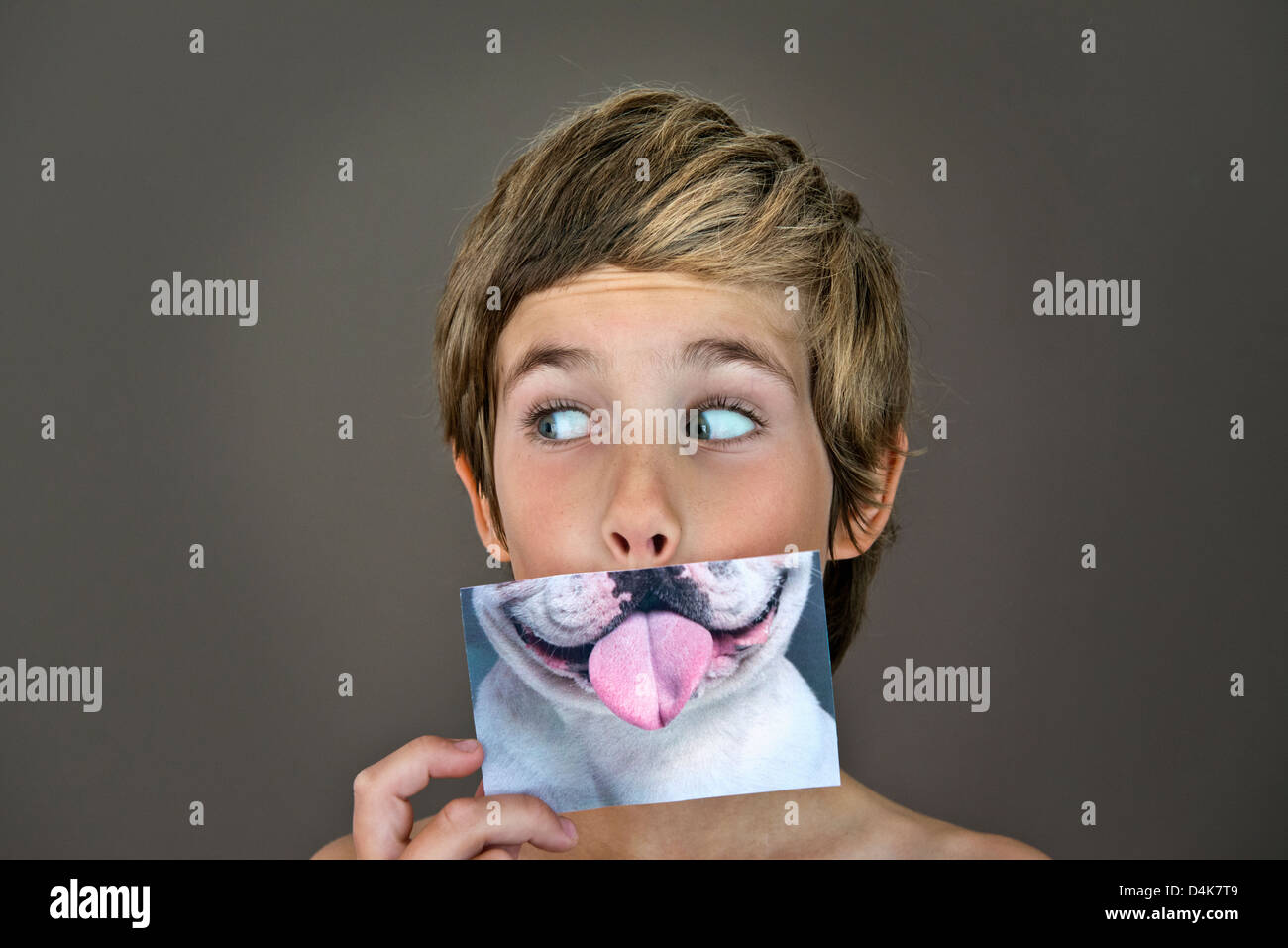 Boy holding picture of dog over face - Stock Image