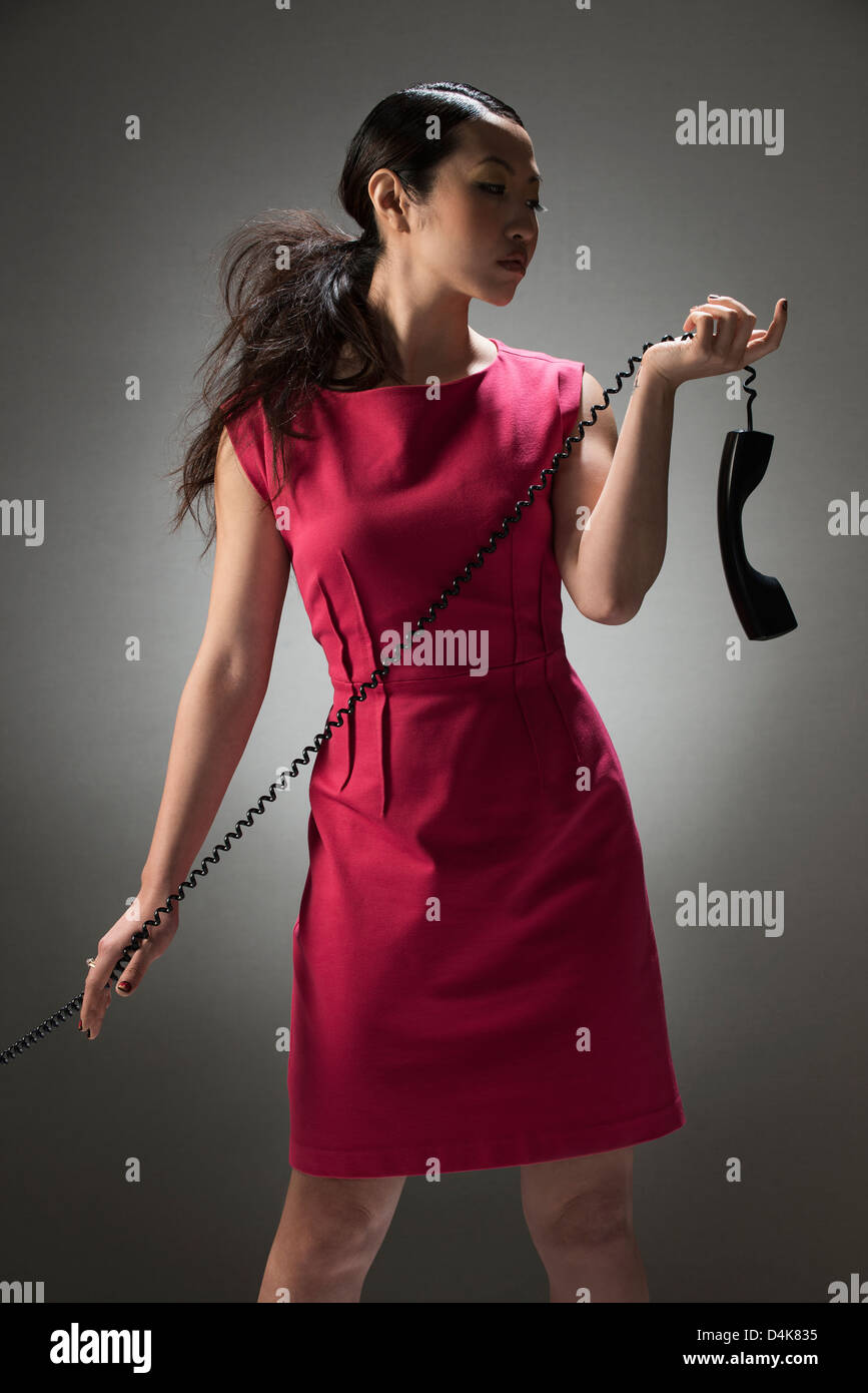 Businesswoman holding telephone by cord - Stock Image