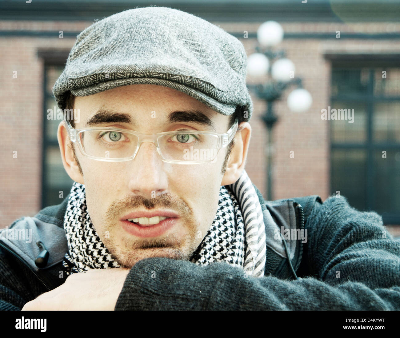 Head and shoulders portrait of man outdoors wearing trendy hat and looking directly at camera - Stock Image
