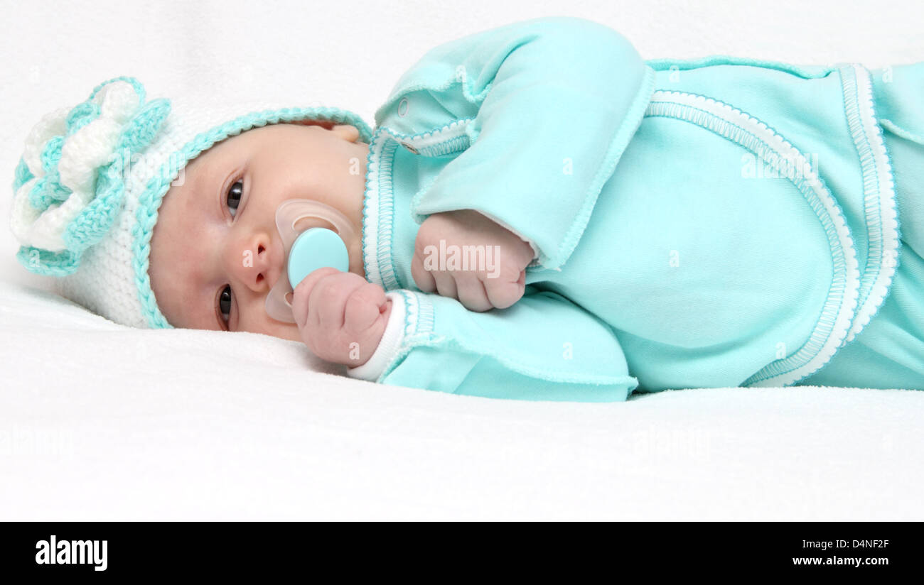 Infant with pacifier looks at the camera - Stock Image
