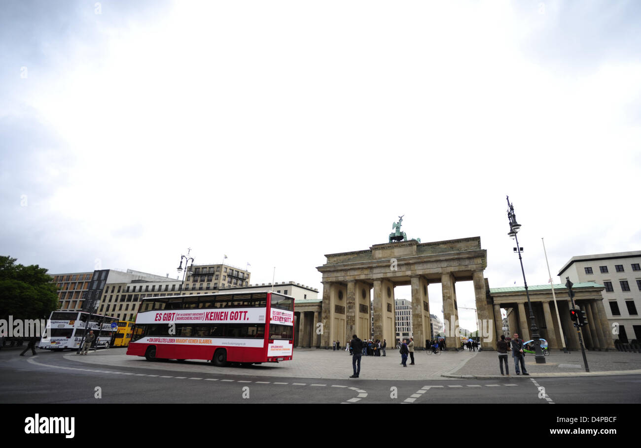 A bus with the writing ?There is (with a probability bordering on certainty) no God? passes Brandenburg Gate in - Stock Image