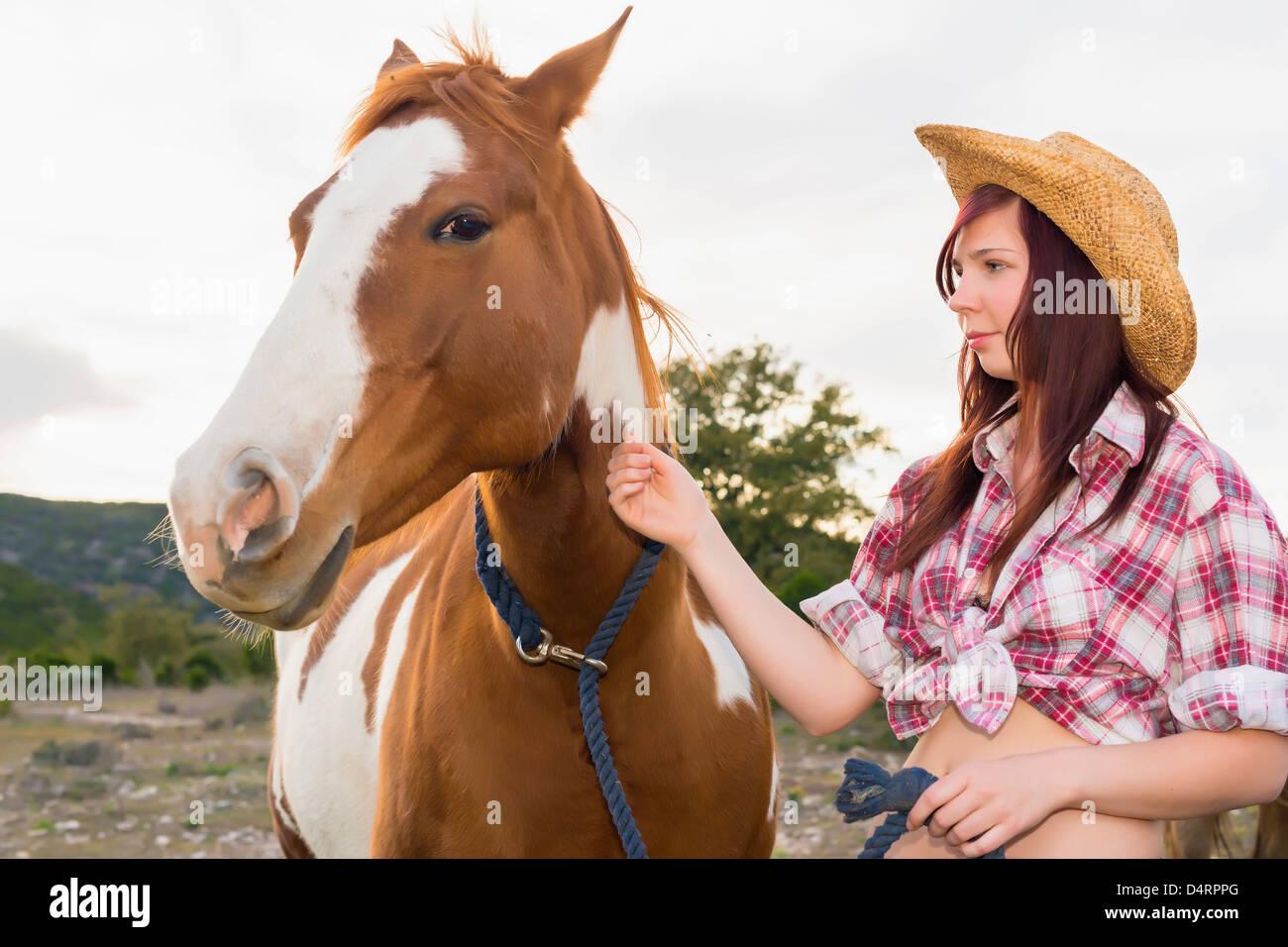 Female teenager petting a horse, Female 19 Caucasian - Stock Image