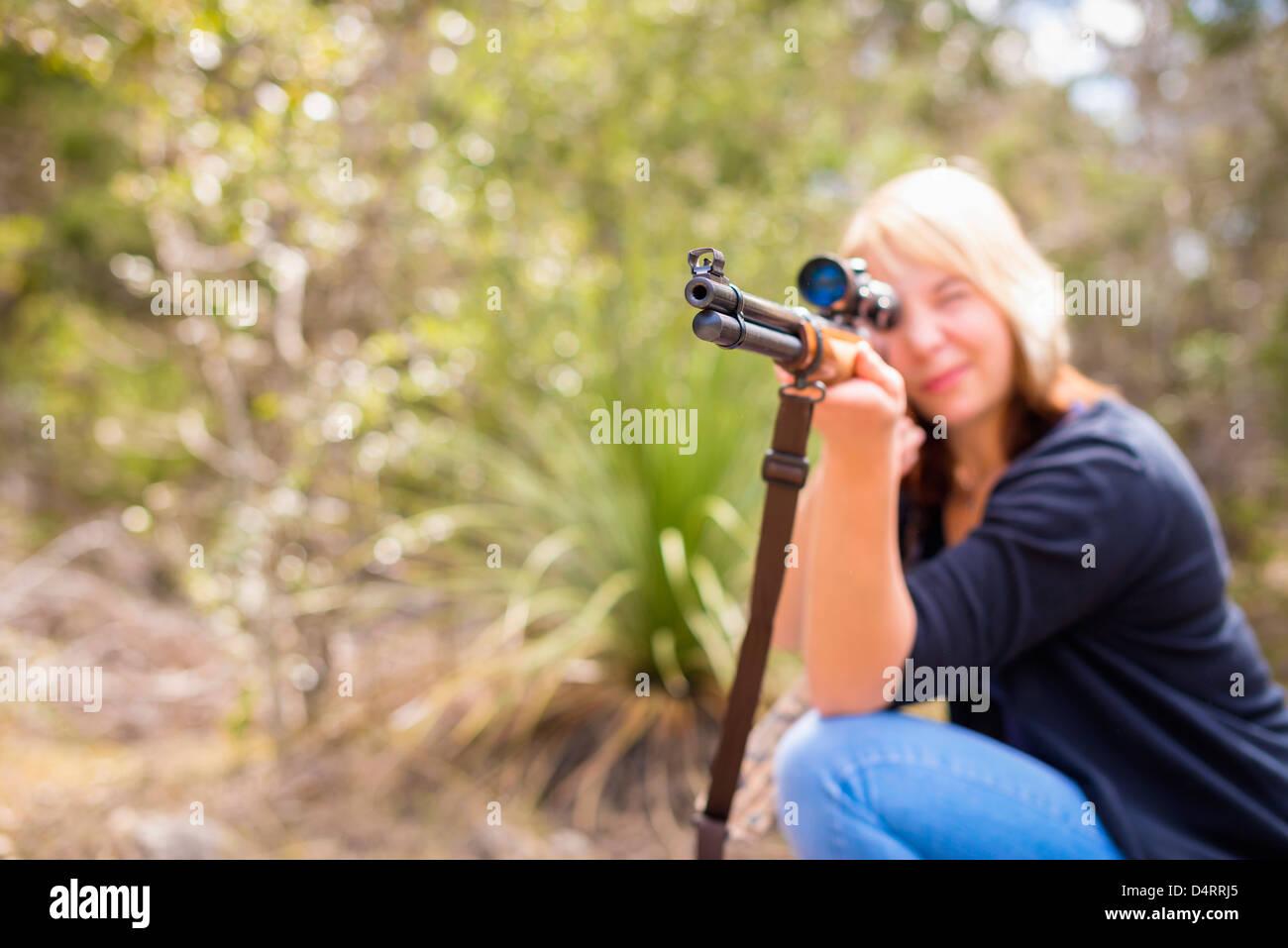 Young woman shooting a hunting rifle firearm, Female 19 Caucasian, Texas, USA - Stock Image