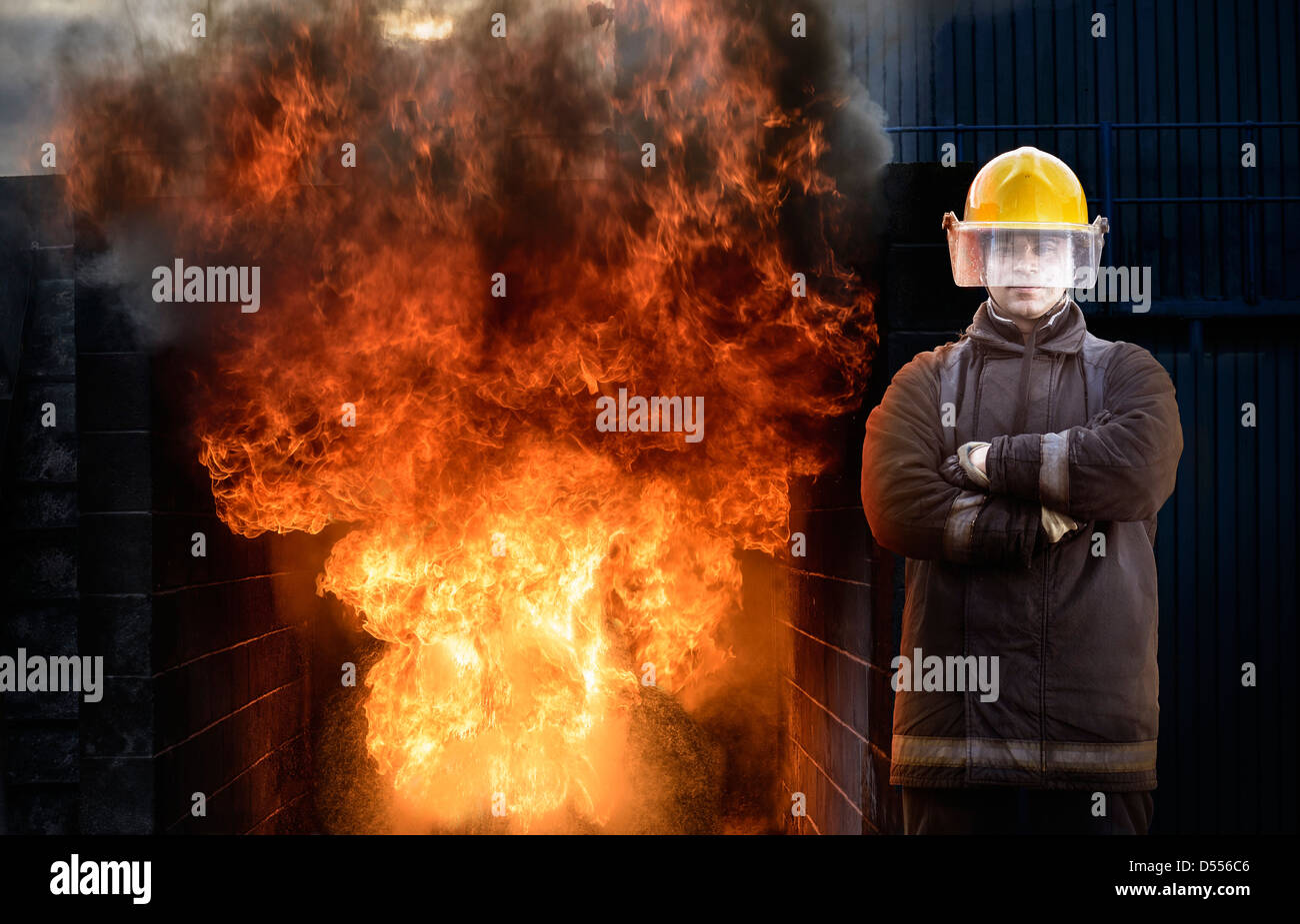 Firefighter standing by blaze - Stock Image