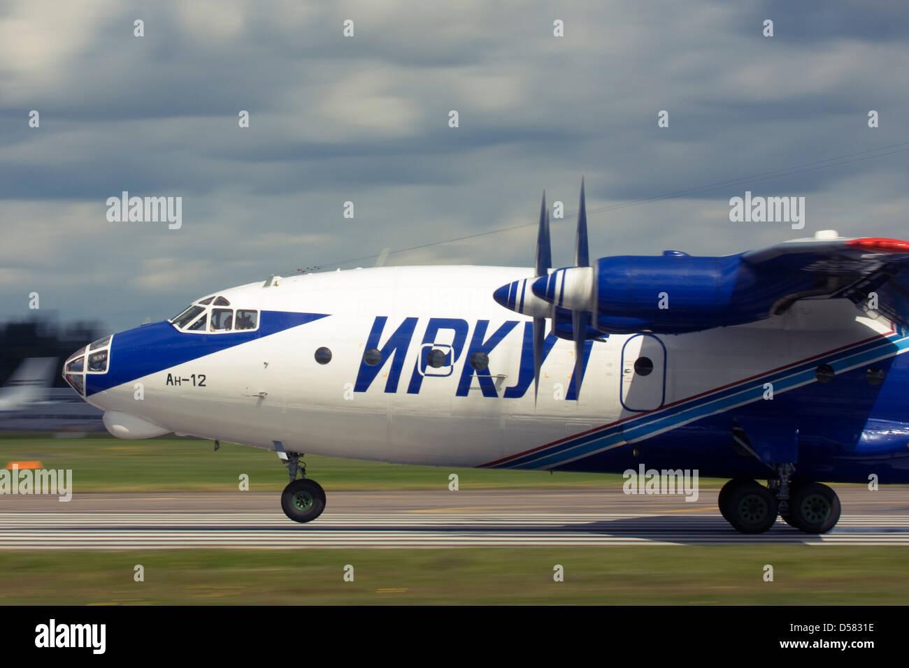 Gromov Air (Irkut-Avia) Antonov An-12 touching down on runway at Farnborough International Airshow 2012 - Stock Image