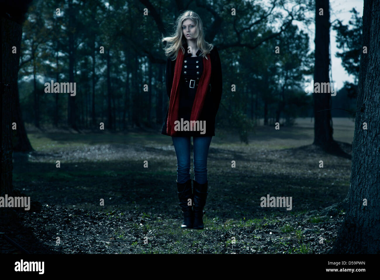 Blond woman black coat red scarf floating outdoors woods blue sky - Stock Image