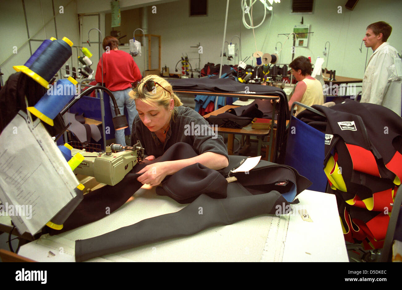 A machinist stitching together a wetsuit. - Stock Image