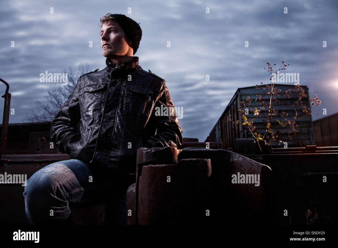 Man standing in rail road yard against stormy sky - Stock Image