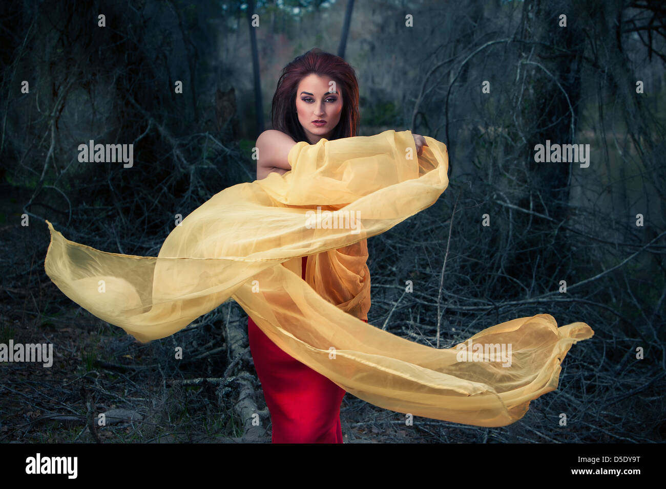 Woman swirling yellow cloth in woods - Stock Image