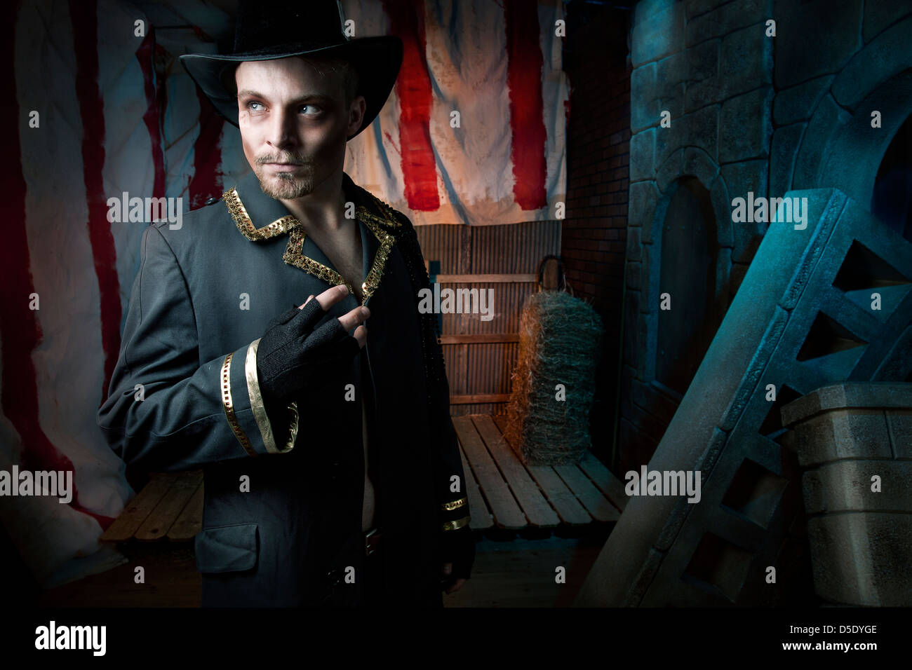 Man with top hat in dark tented alley - Stock Image