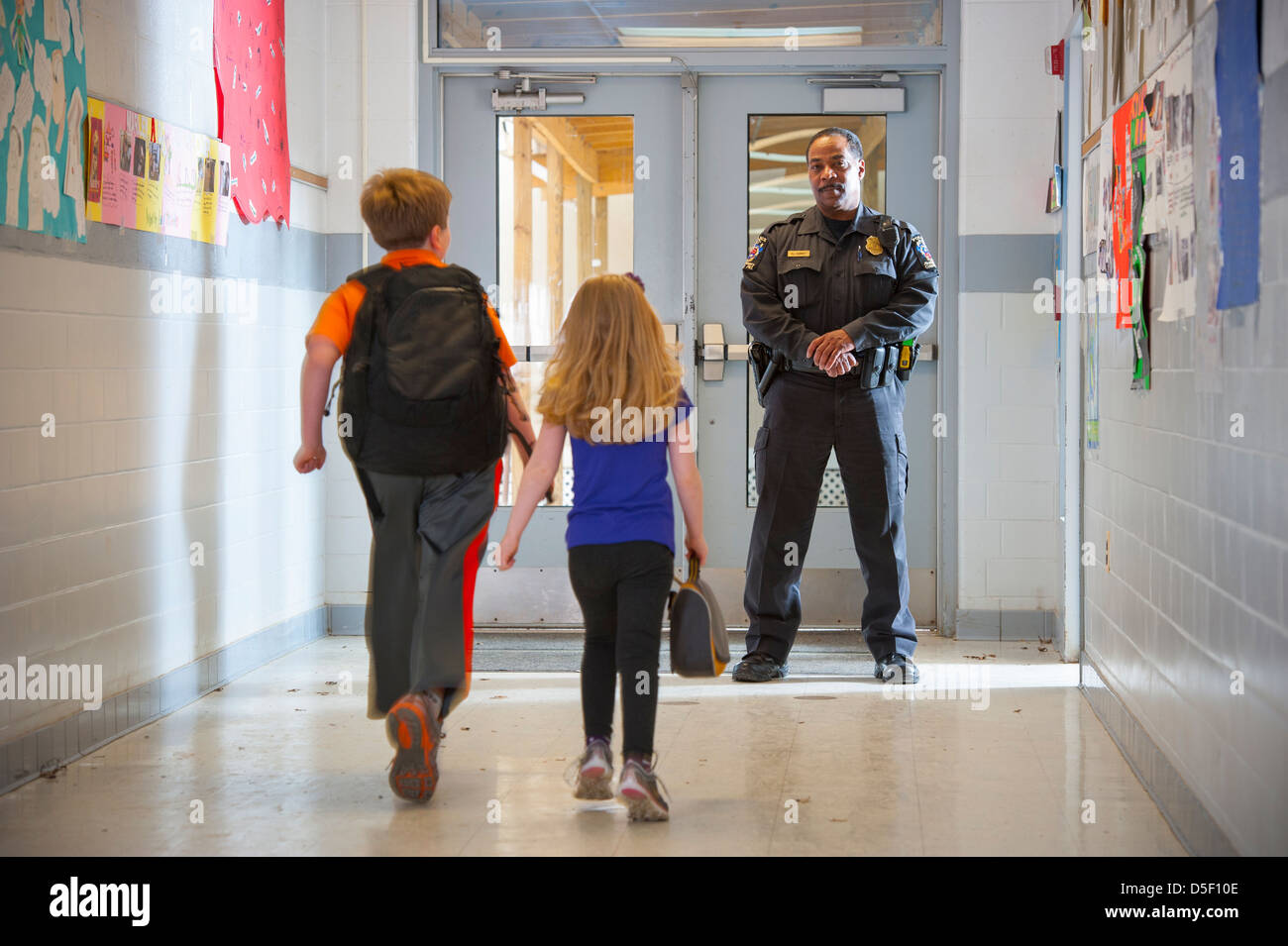 usa-safety-in-public-schools-police-officer-with-boy-and-girl-in-school-D5F10E.jpg
