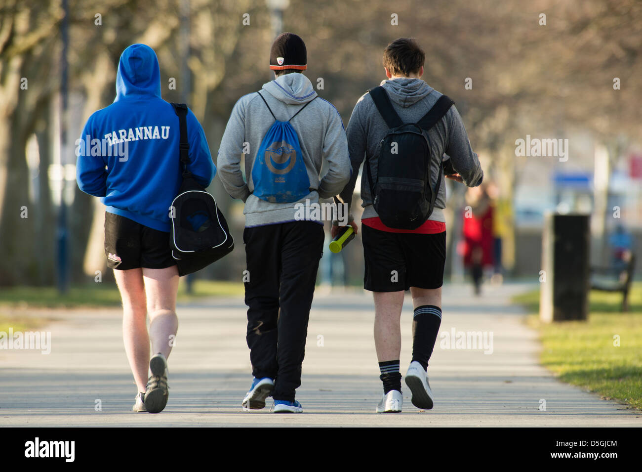 Rear view of three young men with kit bags on their backs walking to or from a sports training session at University, - Stock Image