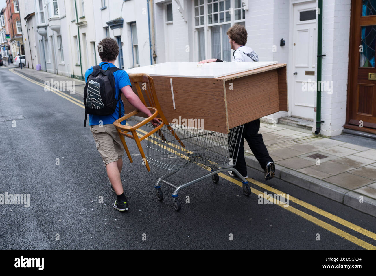 Two students people men moving furniture wheeling a wardrobe on a shopping trolley aberystwyth wales uk Stock Photo