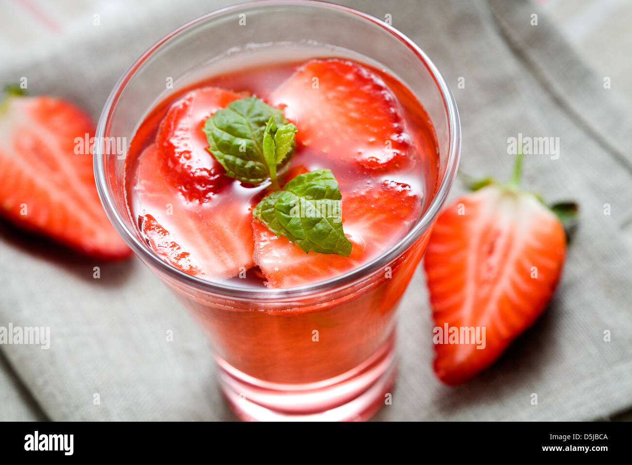 Cold strawberry drink with strawberry slices and mint - Stock Image