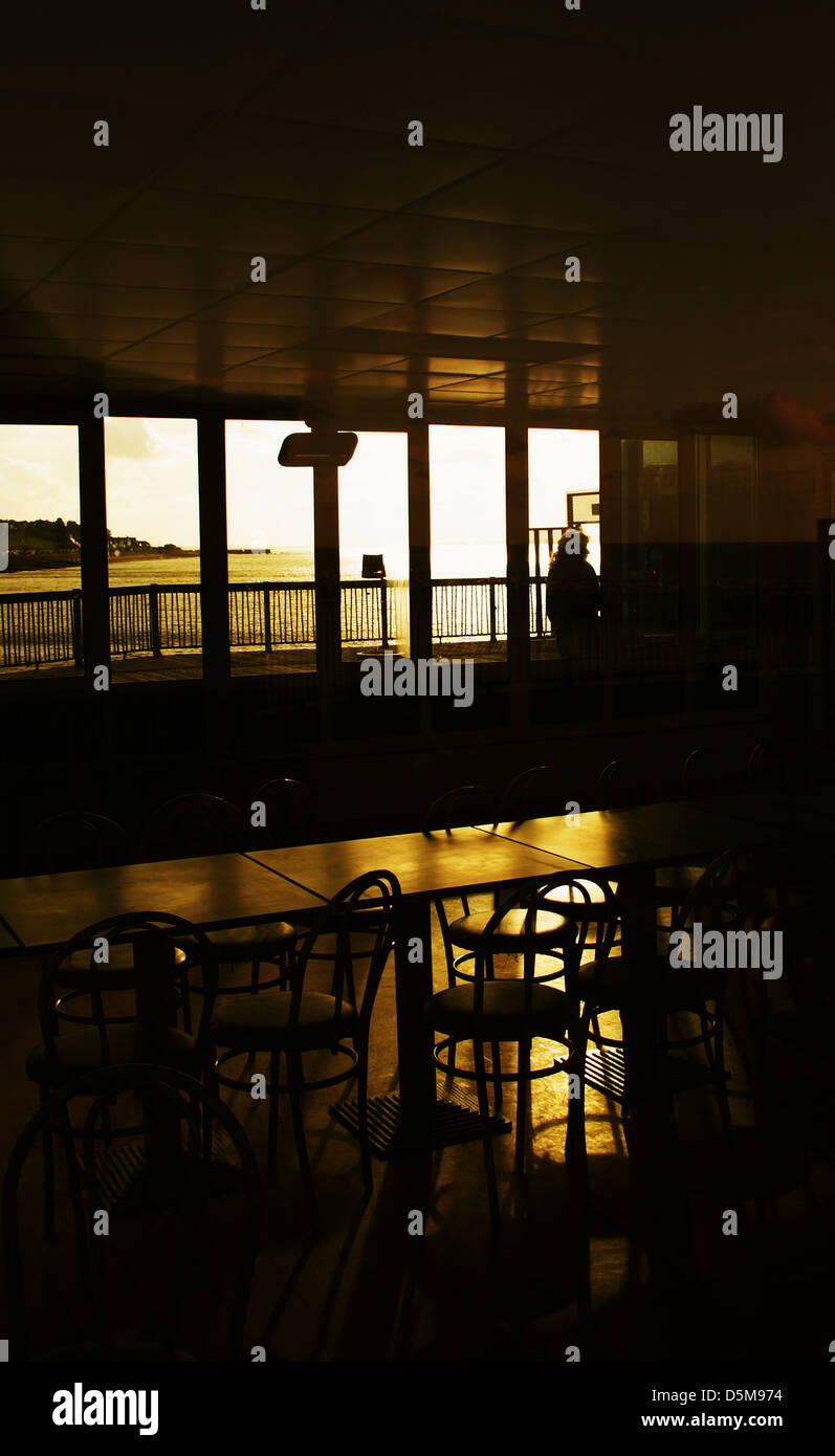 Moody interior of a cafe, looking across empty tables and chairs, golden in colour Stock Photo
