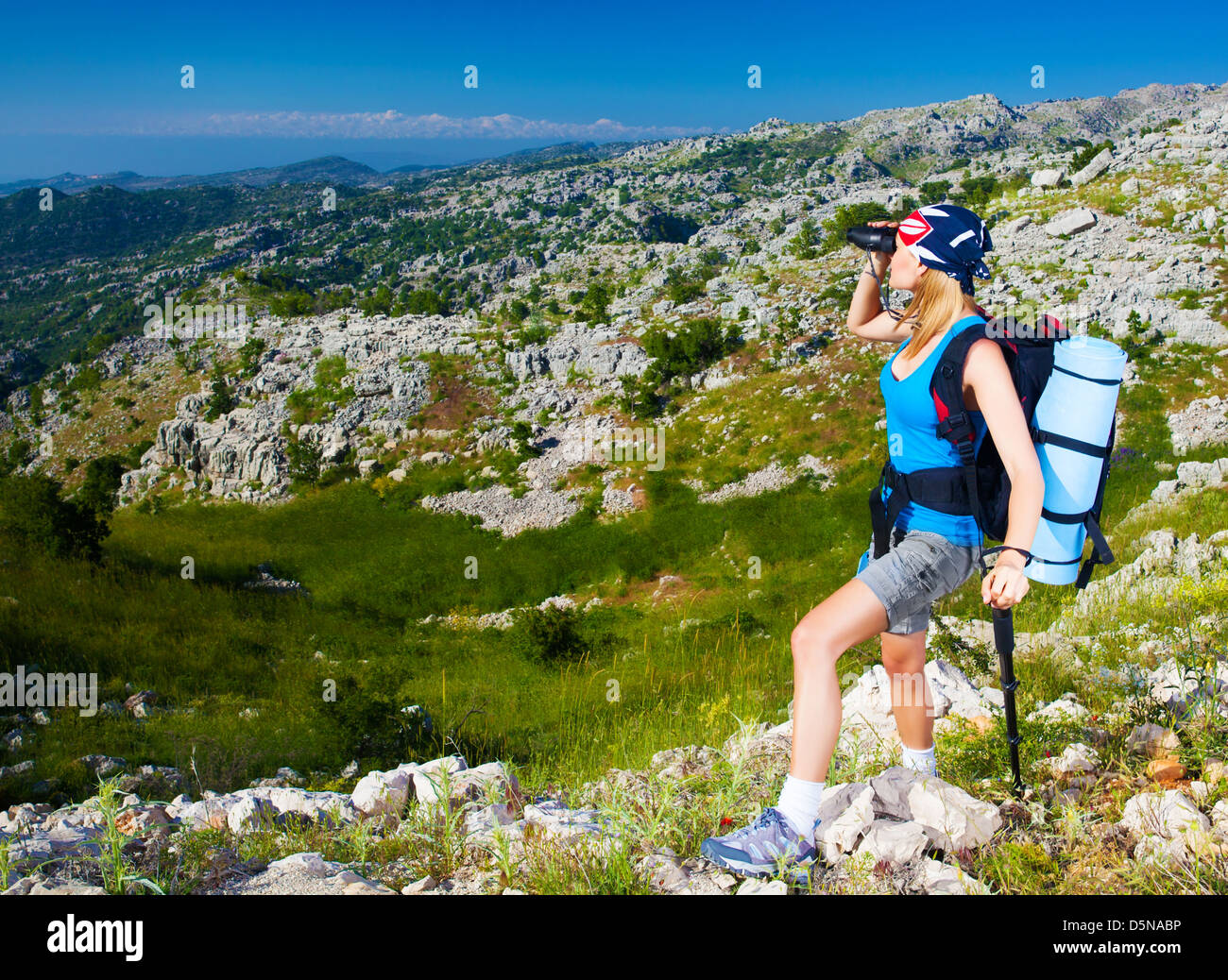 Young active female standing on the top of mountain and watching away in binocular, extreme lifestyle, traveling - Stock Image