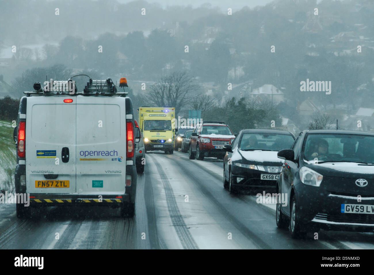 dangerous driving conditions rta road traffic accident snow snowy ice icy blizzard covered slippery police ambulance - Stock Image
