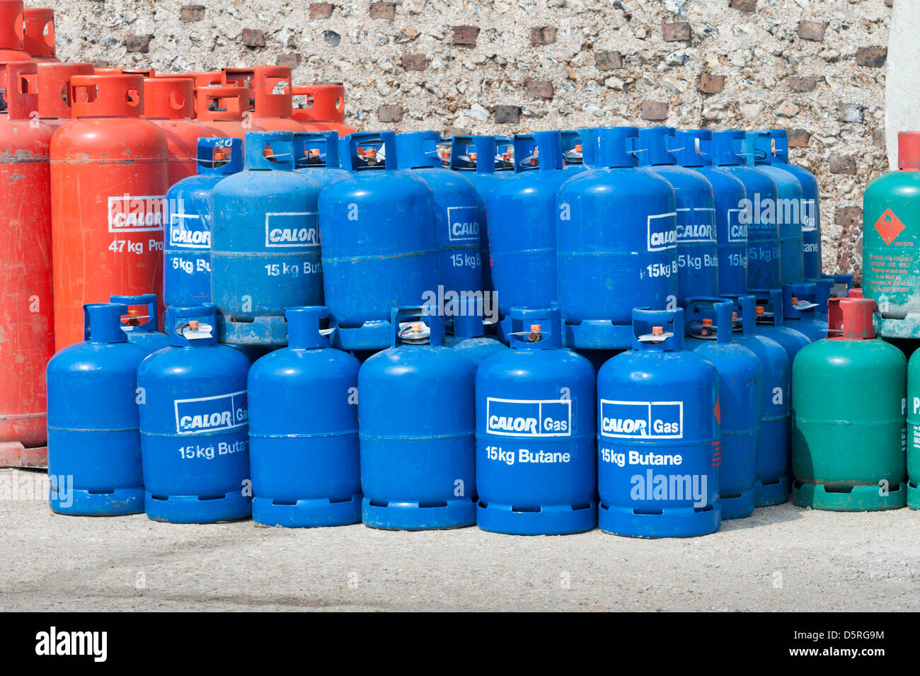 Stacks of red green and blue CALOR GAS butane and Propane cylinders / canisters / bottles - Stock Image