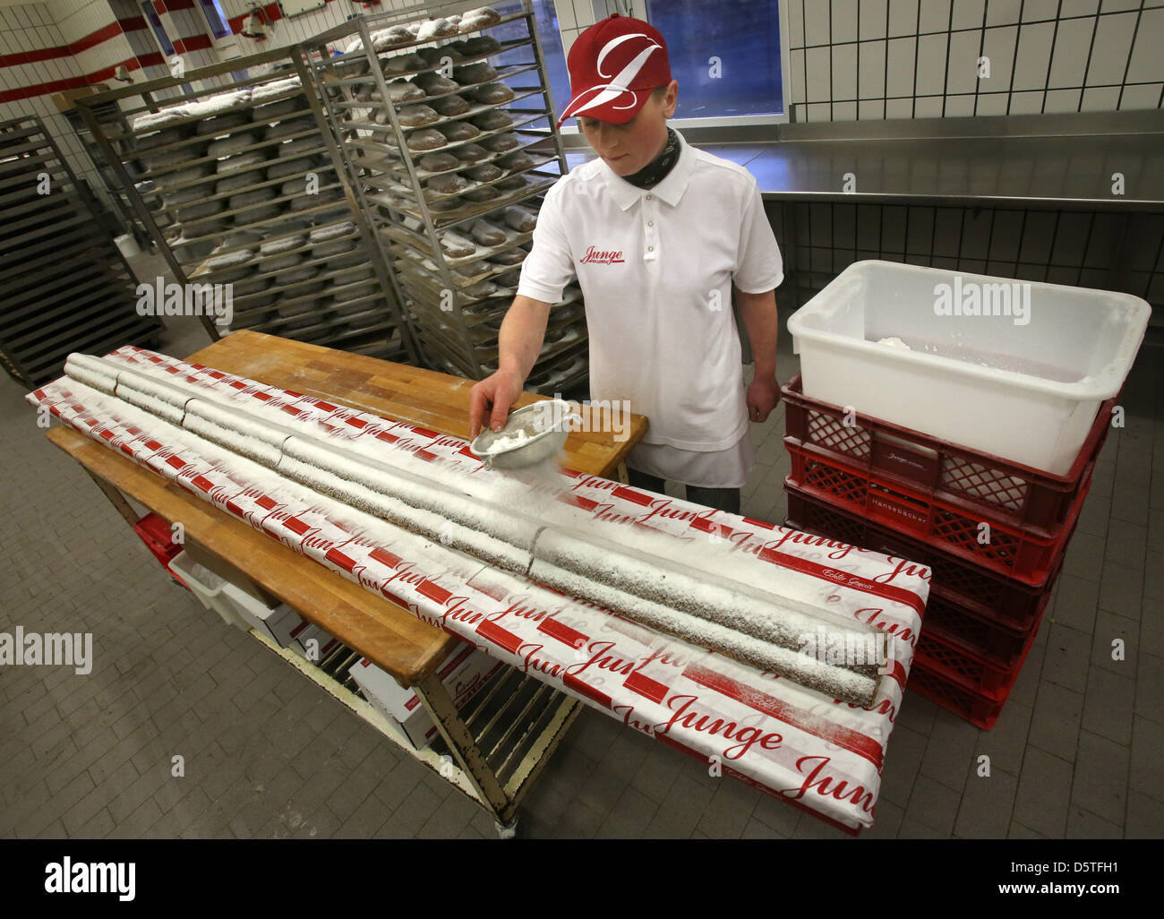 Sandra Jonas dusts the 3.6 m long giant Stollen with icing sugar at the city bakery Junge in Rostock, Germany, 23 - Stock Image