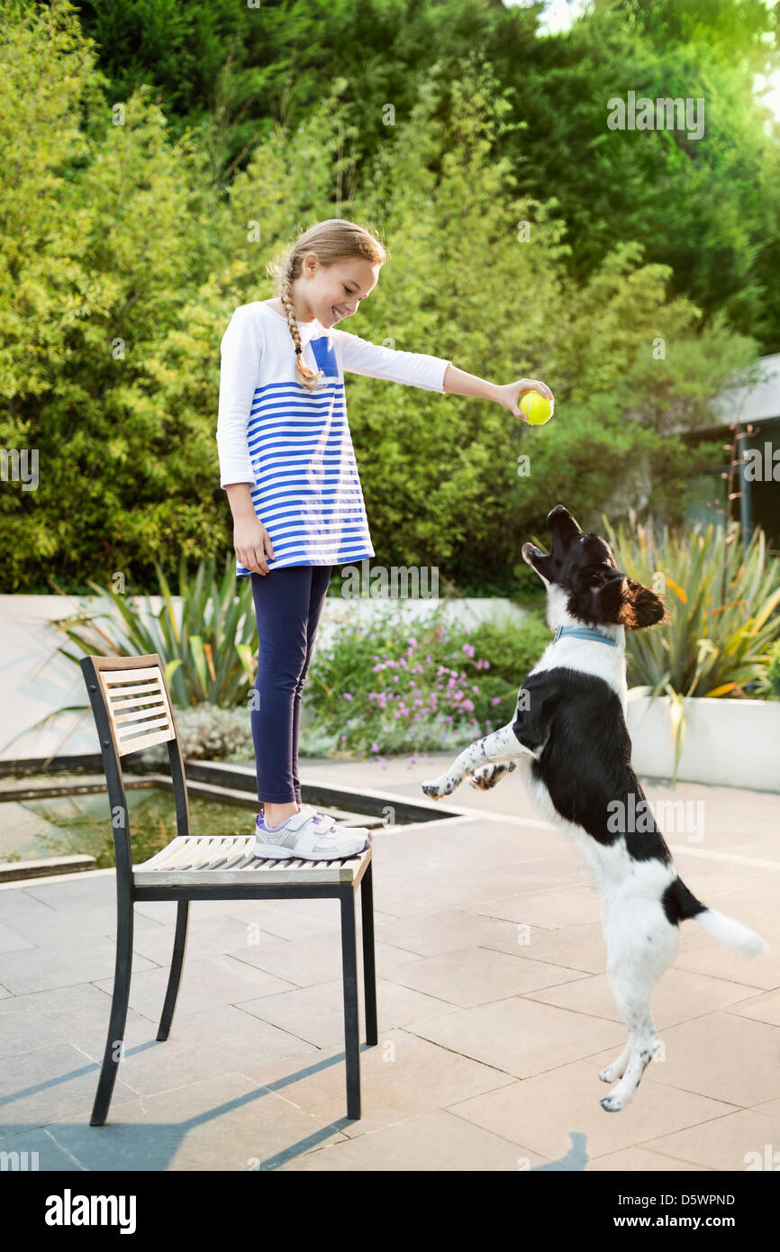 Girl playing with dog outdoors - Stock Image