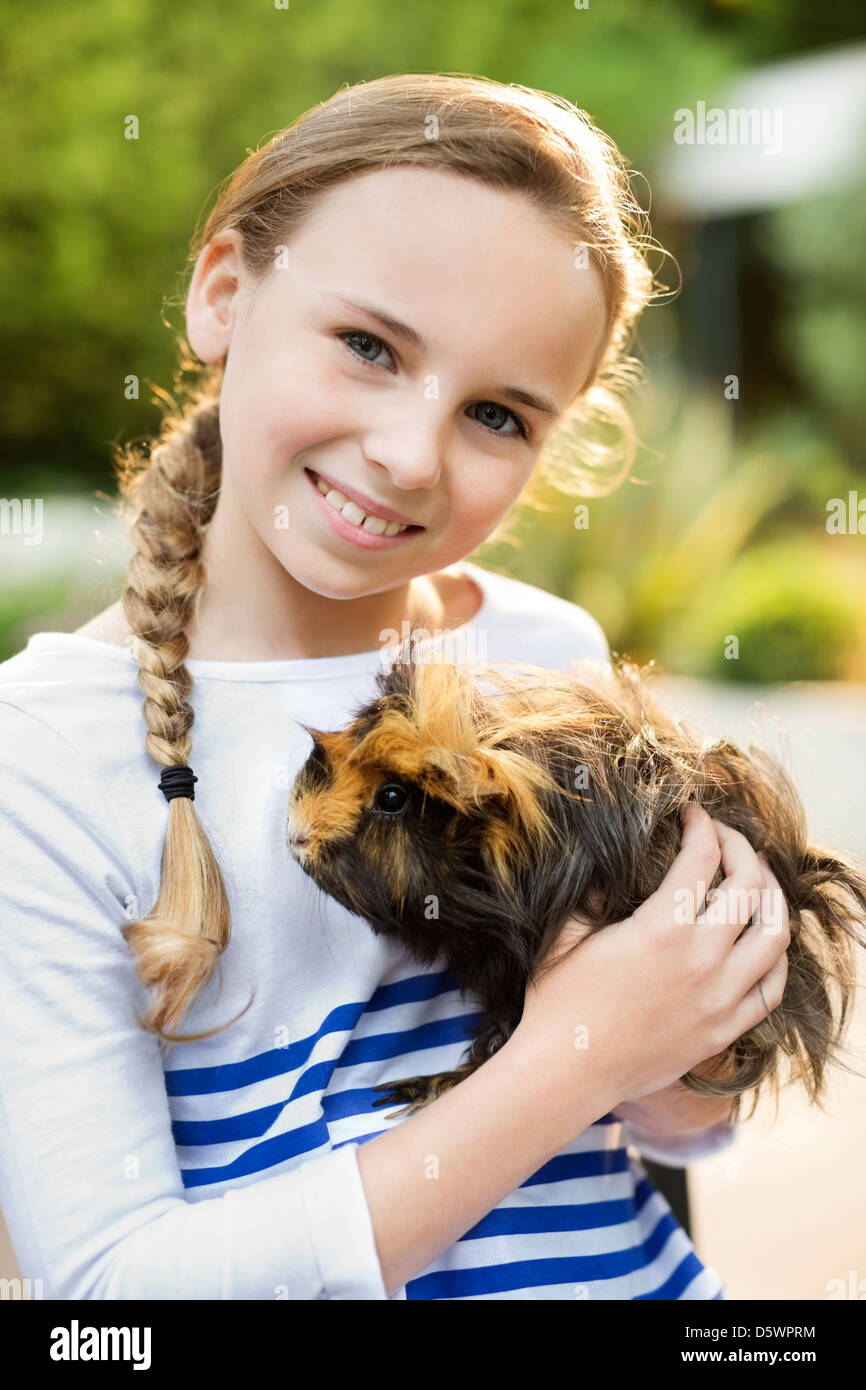 Smiling girl holding guinea pig outdoors - Stock Image