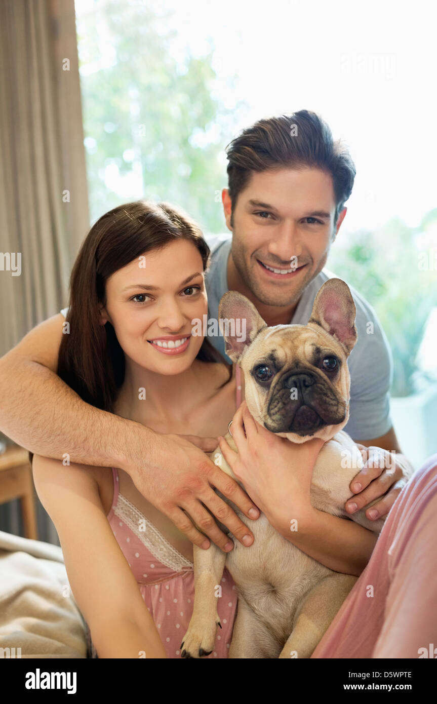 Couple hugging dog on bed - Stock Image