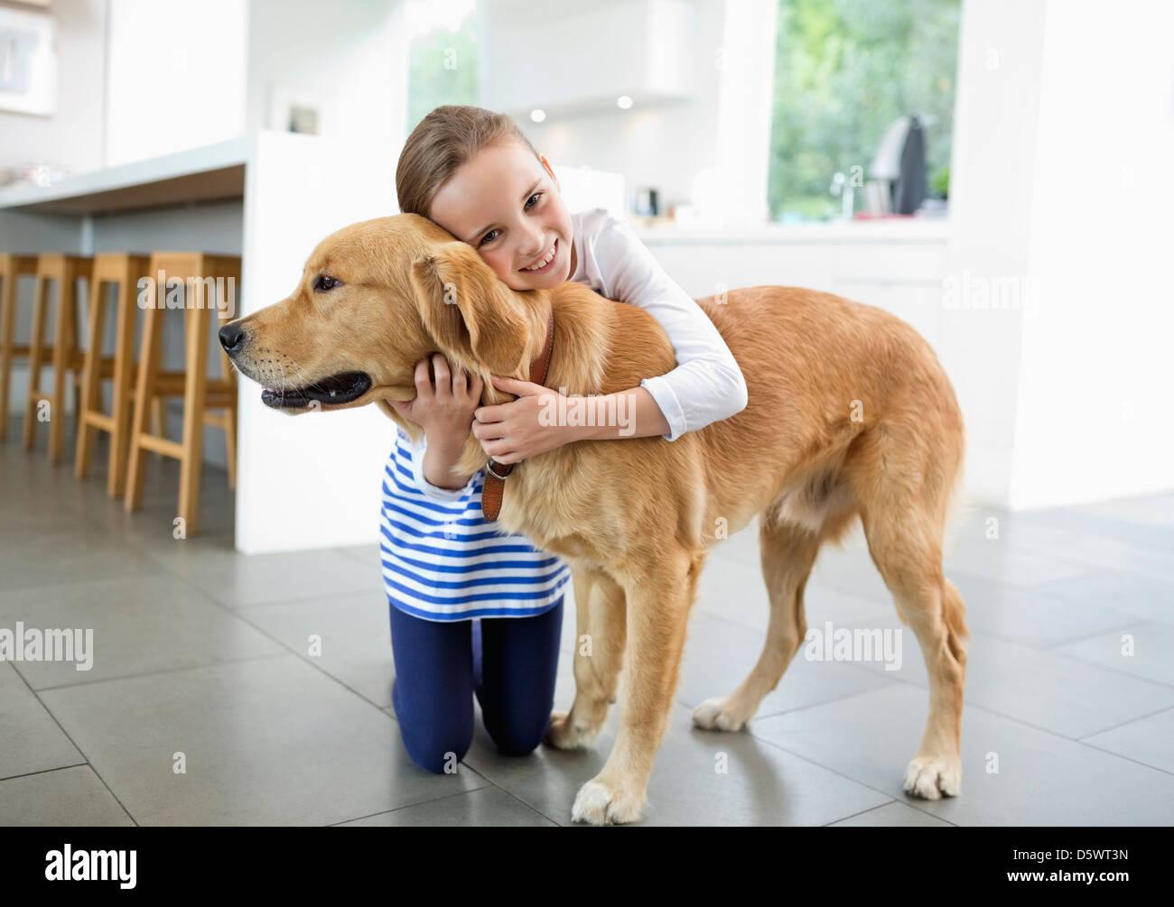 Smiling girl hugging dog in kitchen - Stock Image