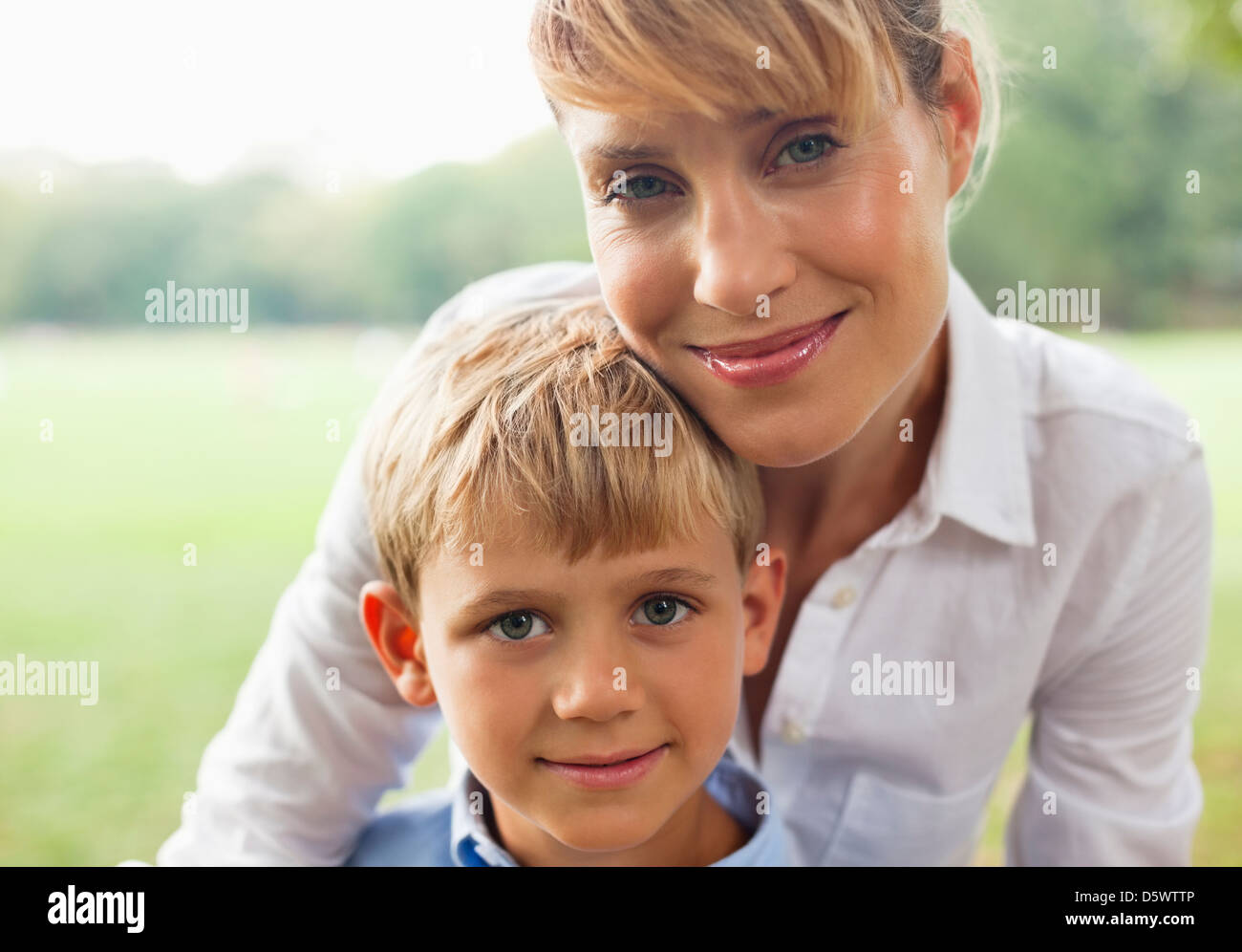 Smiling mother hugging son outdoors - Stock Image