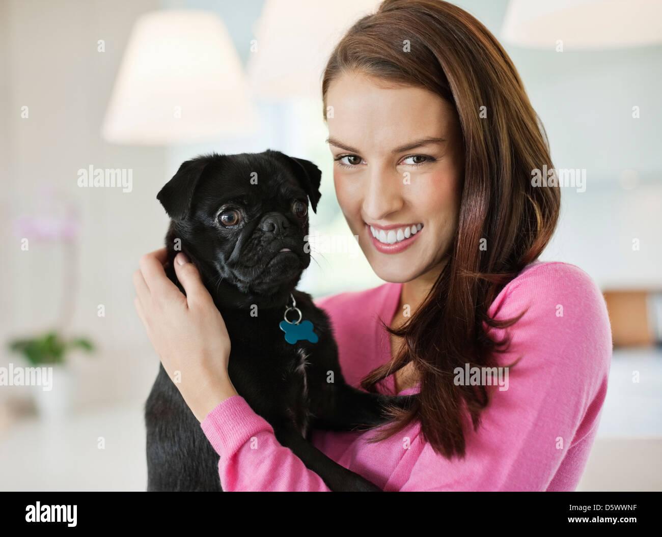 Smiling woman holding dog indoors - Stock Image