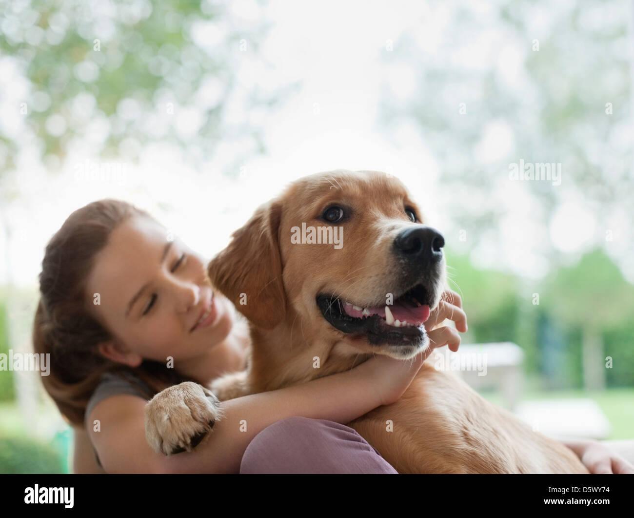Smiling girl hugging dog outdoors - Stock Image