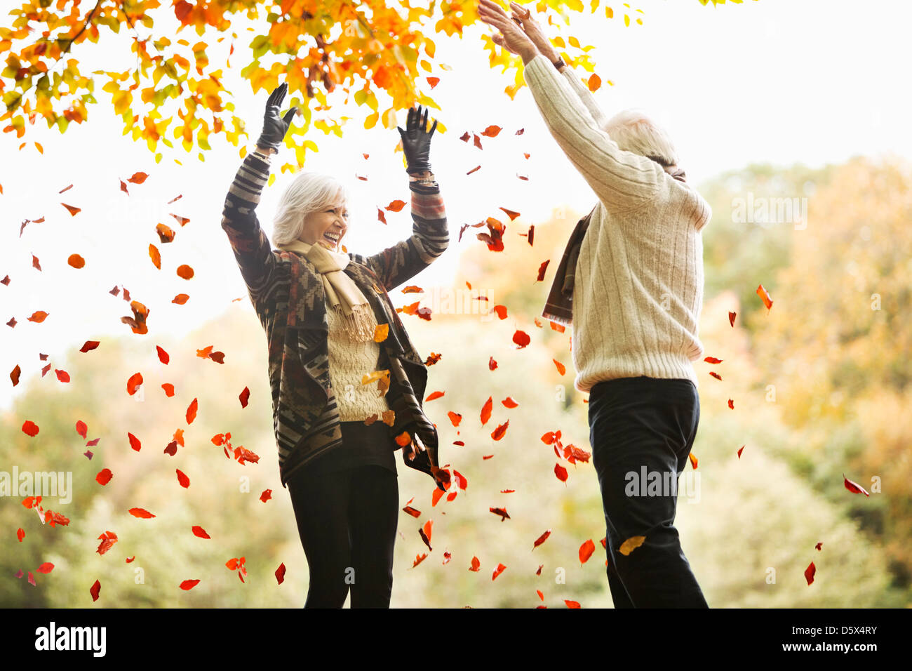 Older couple playing in autumn leaves - Stock Image