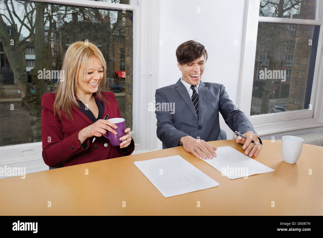 Cheerful young businesspeople with coffee mugs documents t conference table - Stock Image