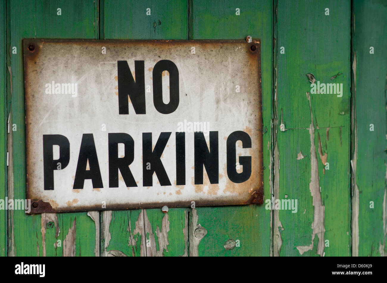 Close Up Of A No Parking Sign On A Green Wooden Garage Door Stock