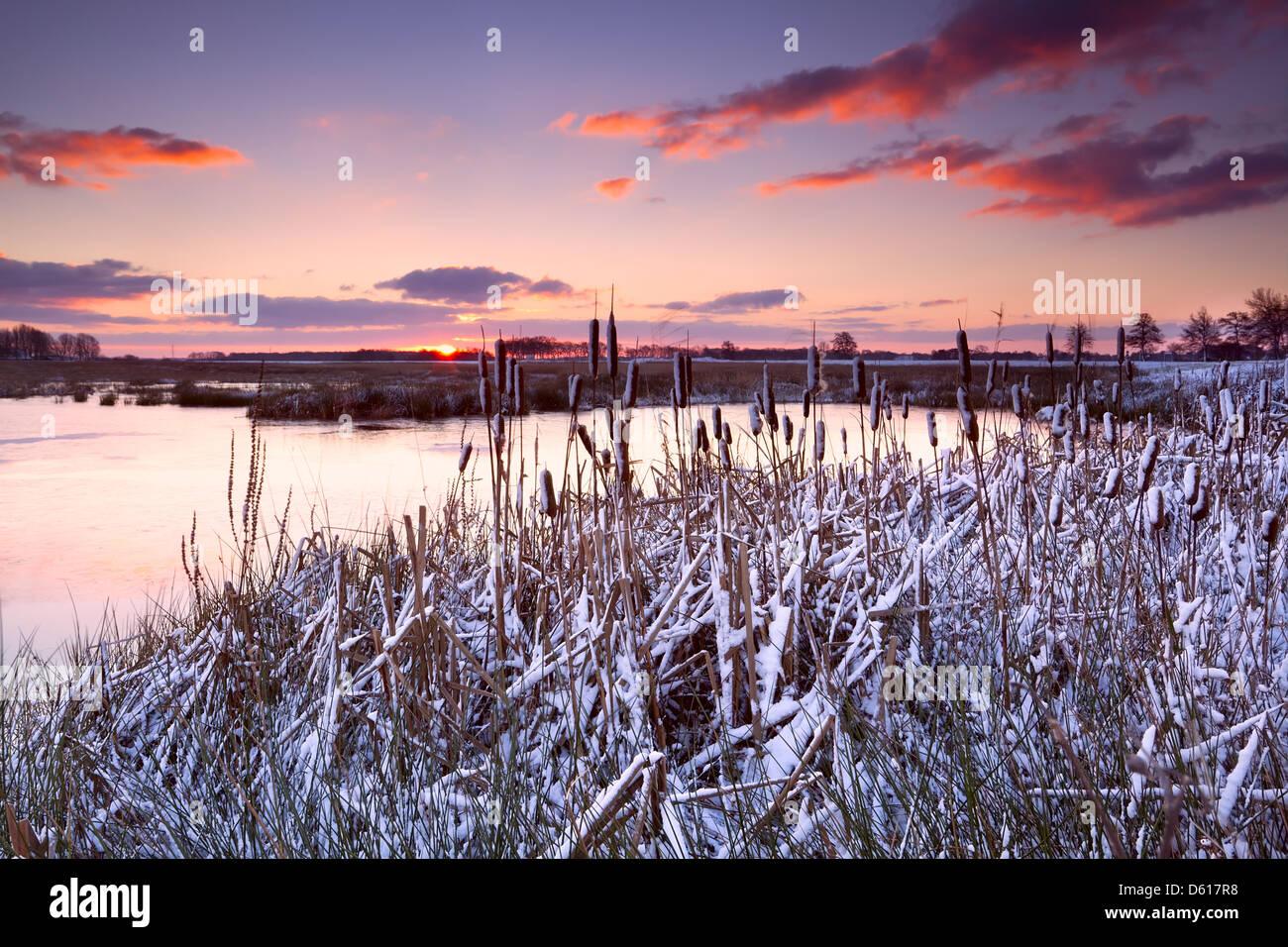 dramatic sunrise over frozen lake - Stock Image