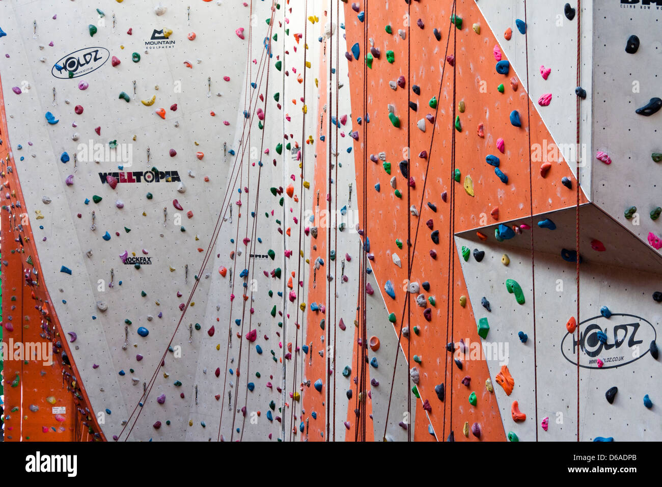 Climbing holds and ropes on an indoor climbing wall. - Stock Image