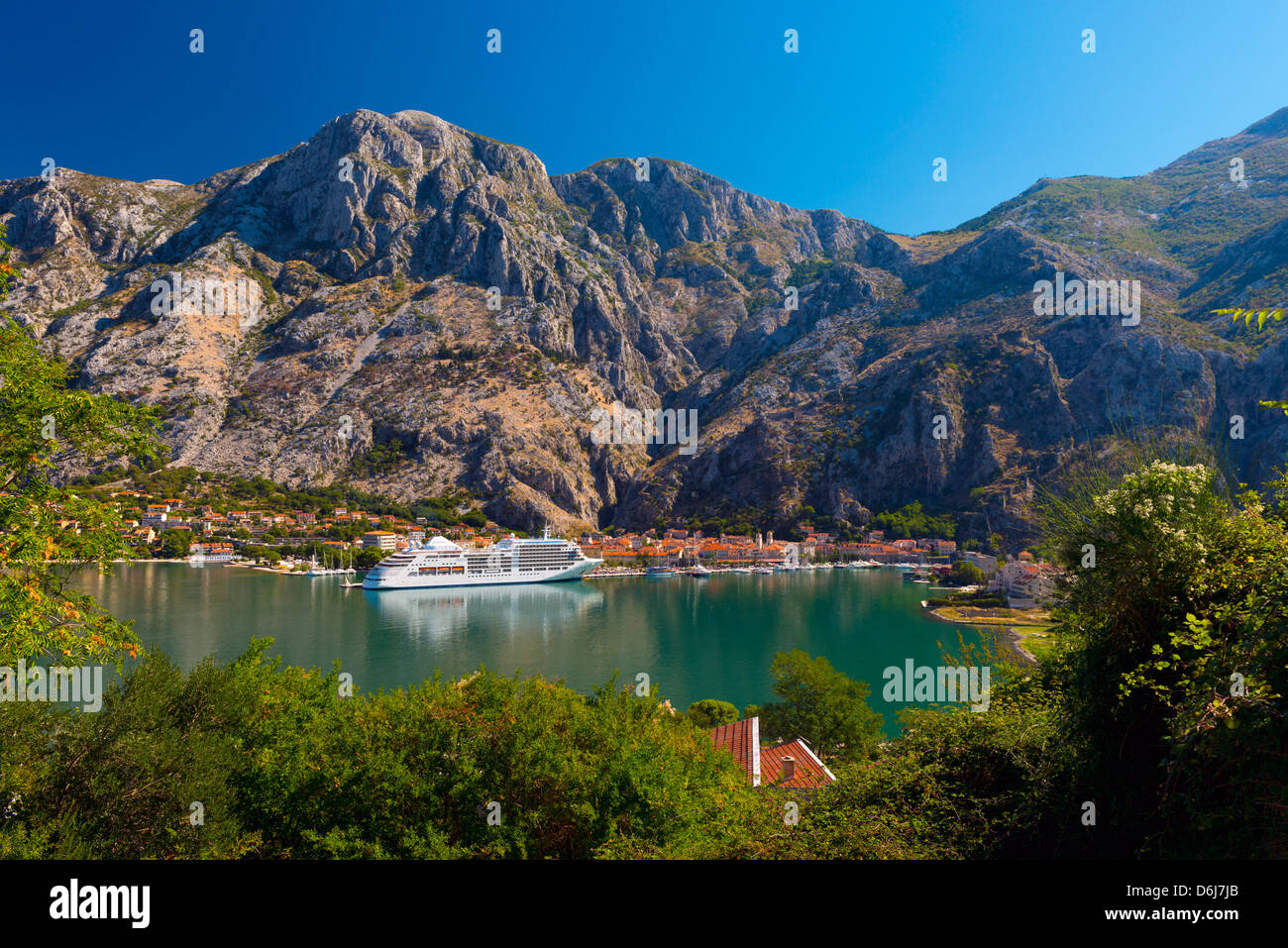 Cruise ship dwarfs the Old Town (Stari Grad), Kotor, Bay of Kotor, UNESCO World Heritage Site, Montenegro, Europe - Stock Image