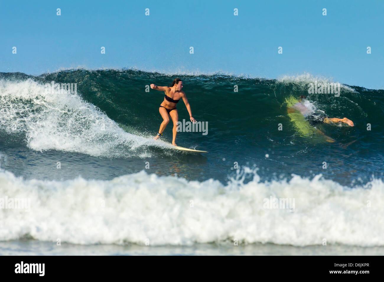 Girl surfer riding wave at popular Playa Guiones surf beach, Nosara, Nicoya Peninsula, Guanacaste Province, Costa - Stock Image