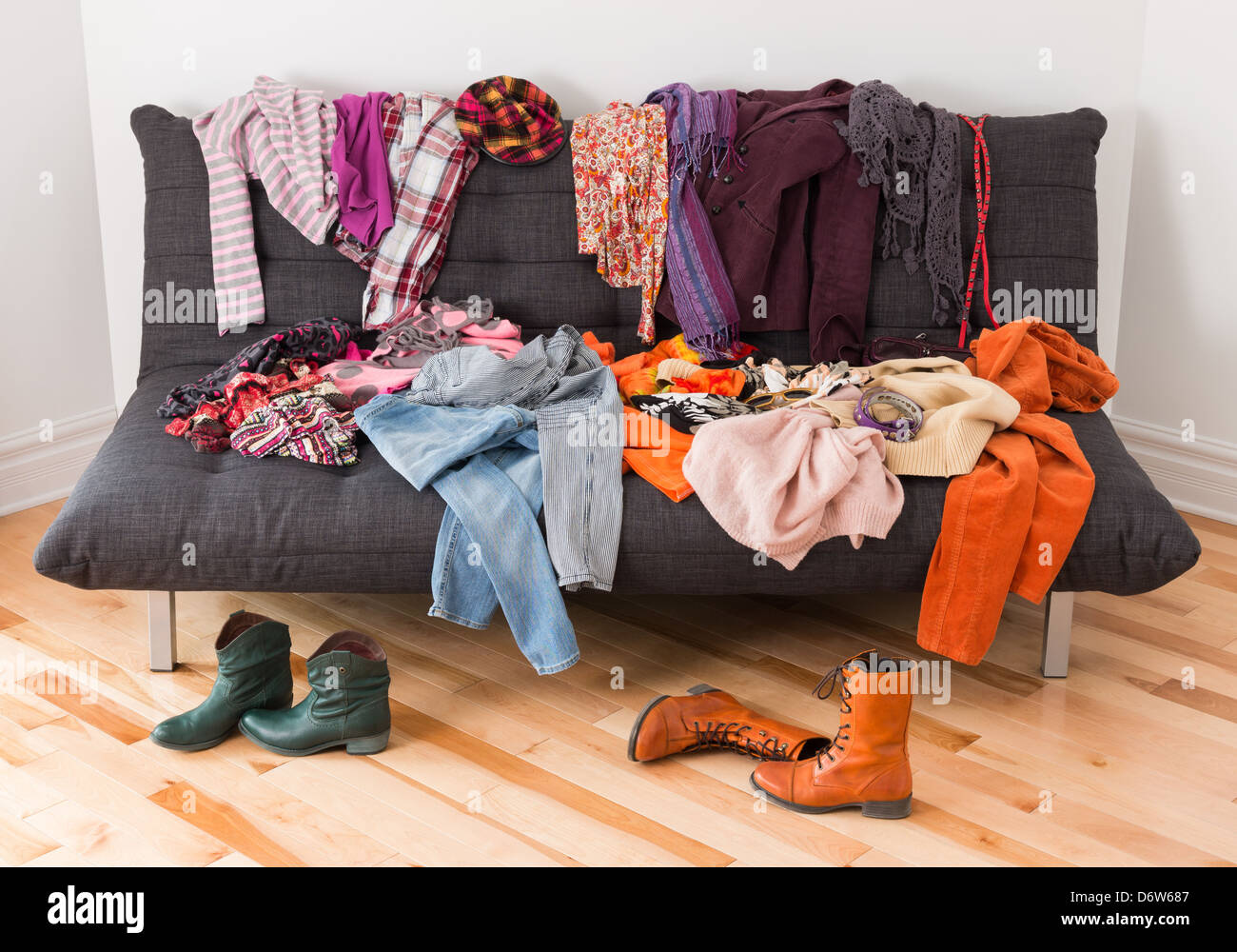 What to wear? Messy colorful clothing on a sofa. Stock Photo