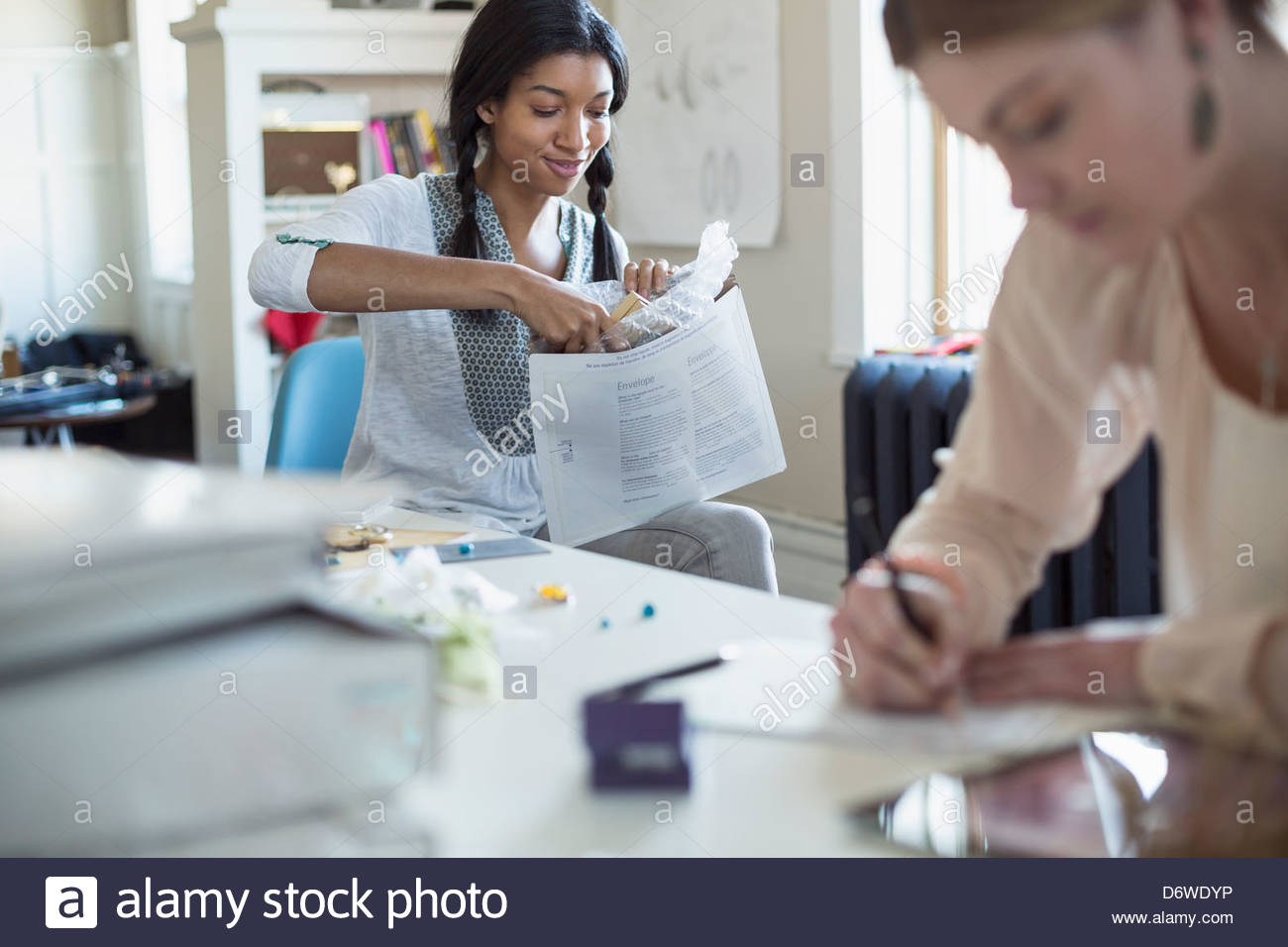 Happy female artist putting box in shipping envelope with colleague in foreground - Stock Image