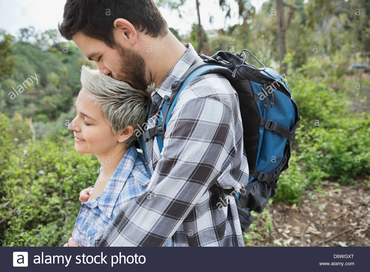 Side view of man kissing woman on head in forest - Stock Image