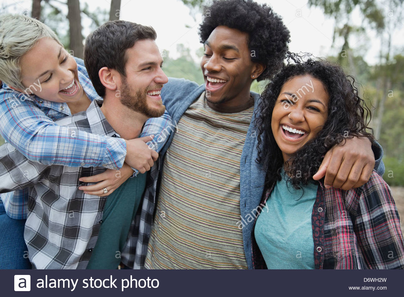 Group of friends having fun together in forest - Stock Image