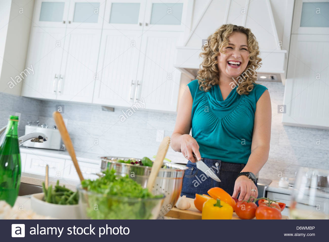 Happy mature woman cutting vegetables in kitchen - Stock Image