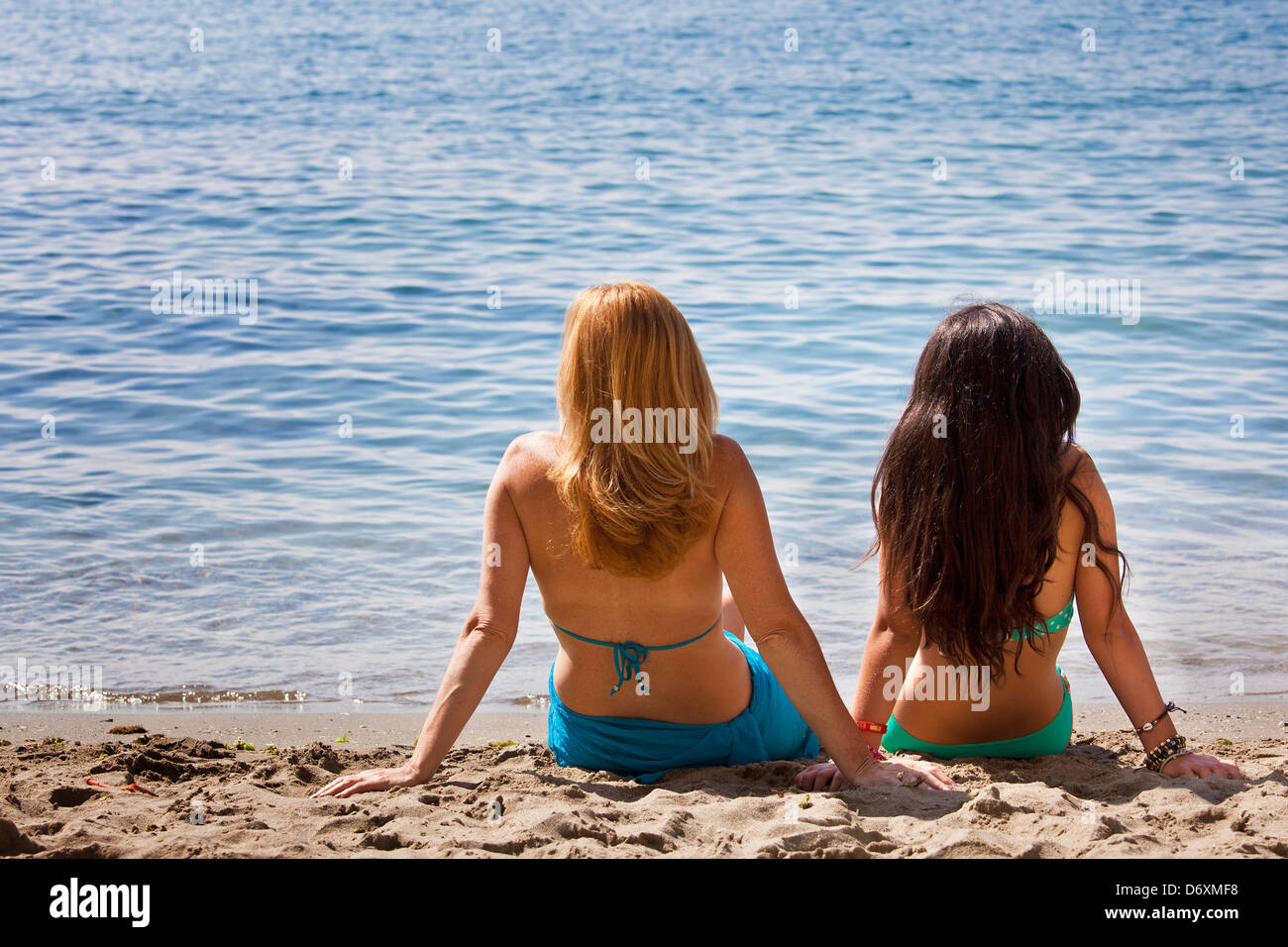 a mother and her teenager girl  looking  the sea at the beach - Stock Image