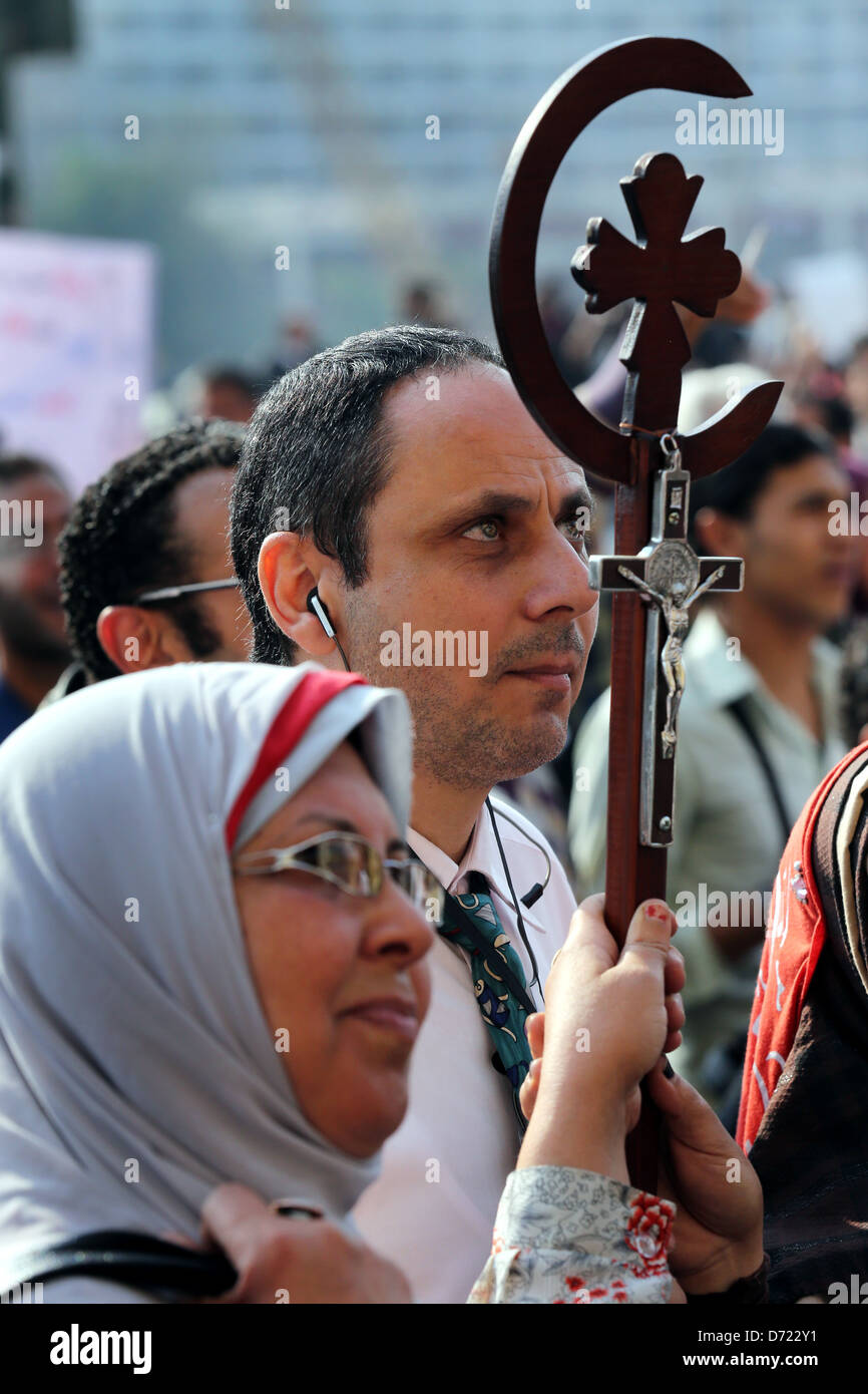 An Egyptian muslim-christian couple holds a cross during a mass rally in Tahrir Square, Cairo, Egypt - Stock Image